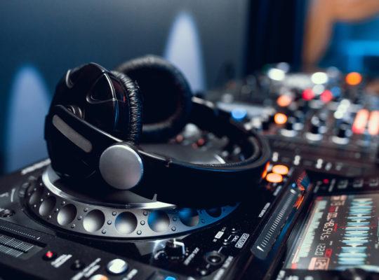 professional headphones on dj board in night club