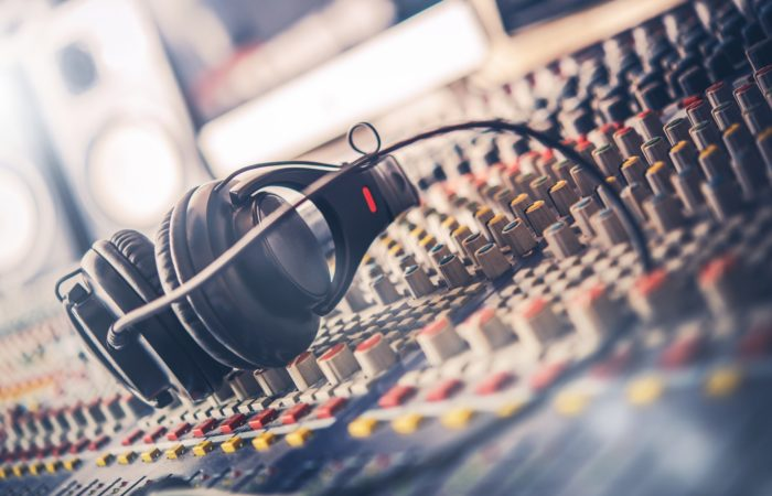 Mixer and Professional Headphones in the Recording Studio. Sound Mixing Desk. Sound Mastering For Radio and TV Broadcast.